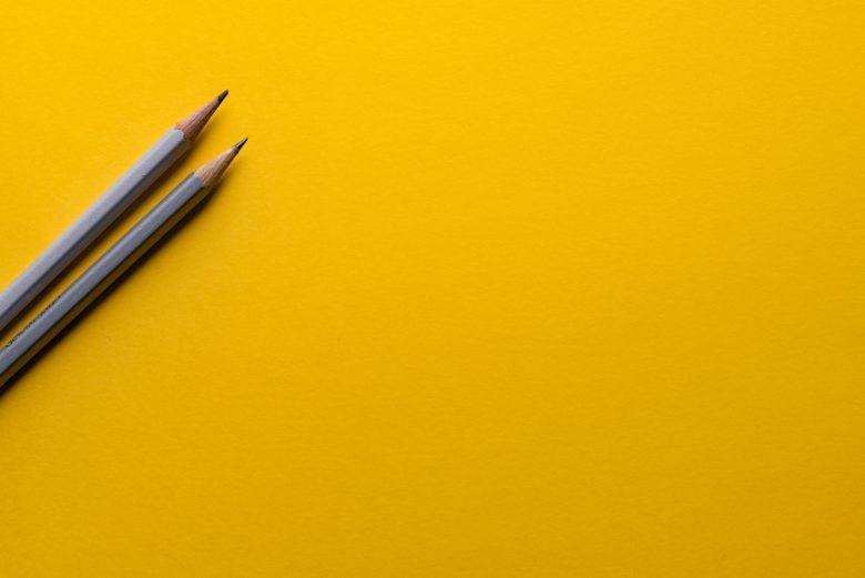 Två blyertspennor mot gul bakgrund